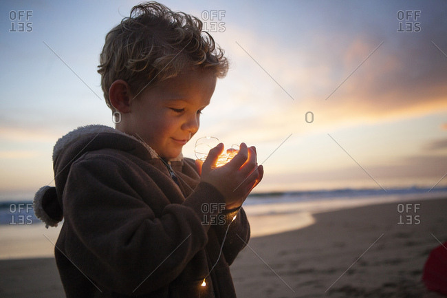 Toddler boy on the beach looking at lights and smiling