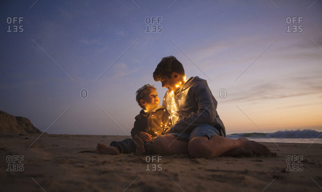 Brothers sitting on the beach at sunset with holiday lights