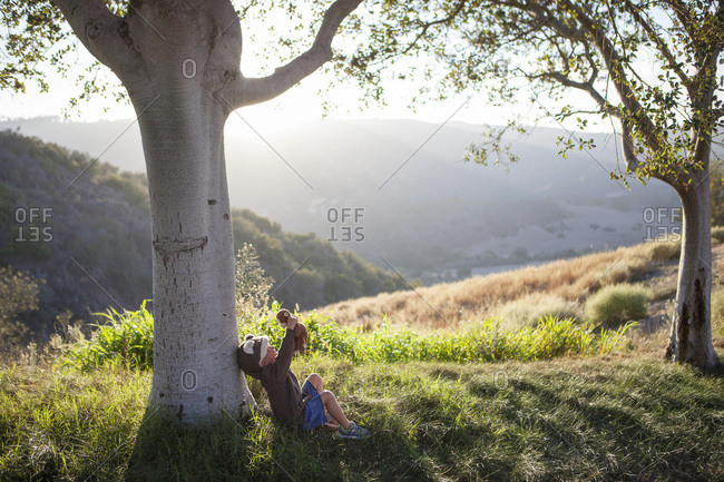 Toddler boy sitting under a tree with a stuffed animal