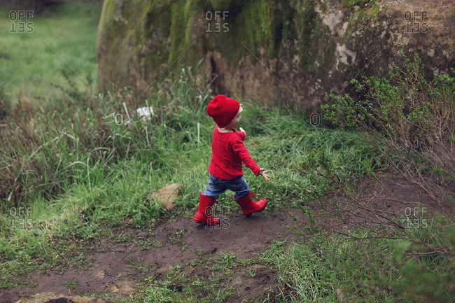 Toddler boy in red walking a trail