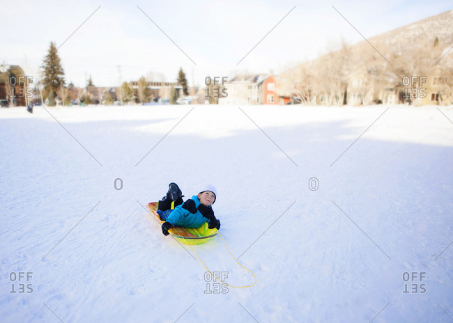 Toddler Boy sledding in a park in the snow
