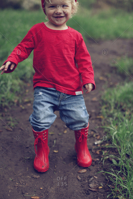 Toddler boy in red outfit walking a trail