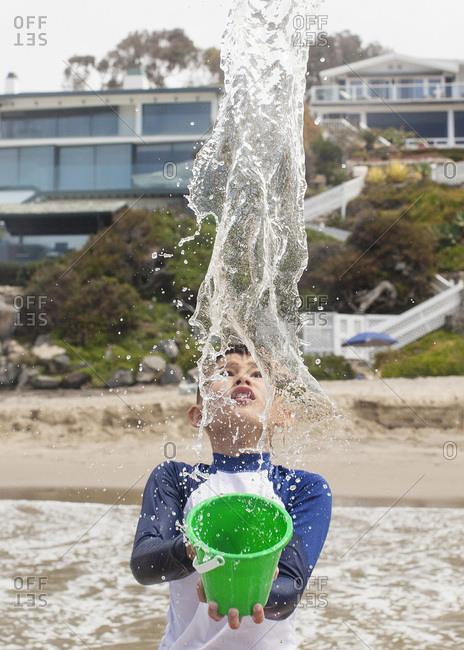 Boy splashing water in the ocean from a bucket