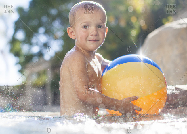 Toddler boy in a pool holding a beach ball
