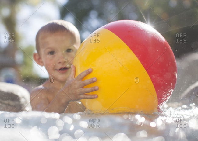 Toddler boy in a pool with a beach ball