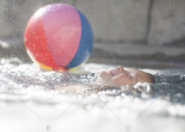 Toddler boy floating in a pool with a beach ball
