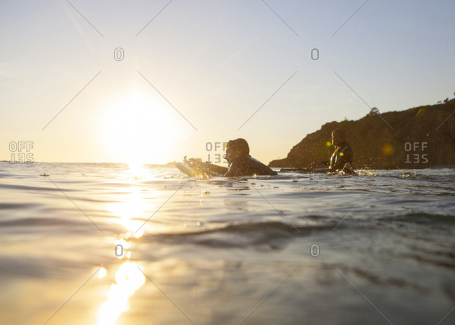 Father and son body boarding in the ocean at sunset