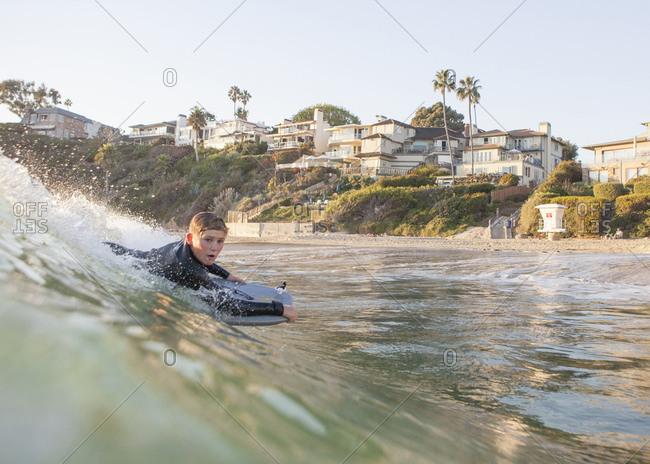 Boy body boarding on a wave in the ocean