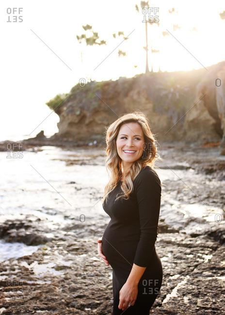 Pregnant woman walking on the beach