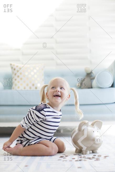 Preschool girl saving money with a piggy bank