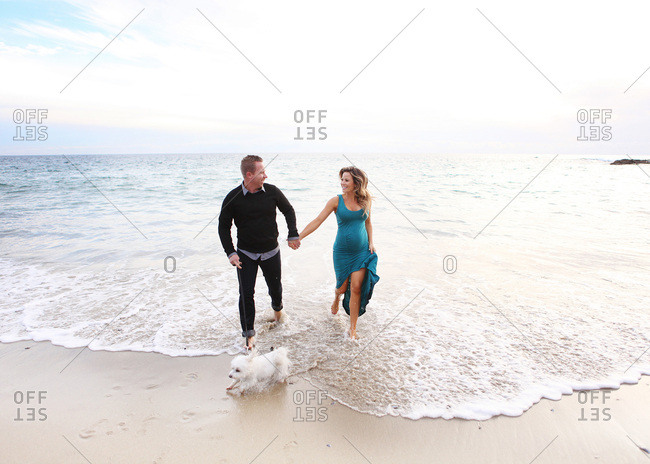 Expecting couple walking on the beach