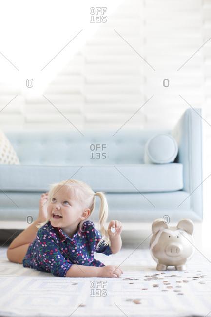 Preschool girl counting money in her piggy bank