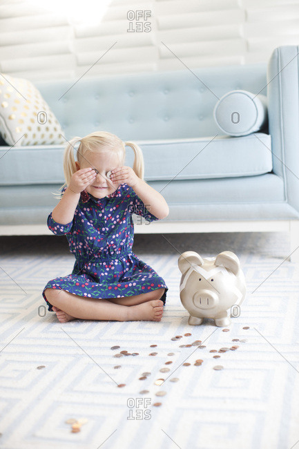 Preschool girl playing with money in her piggy bank