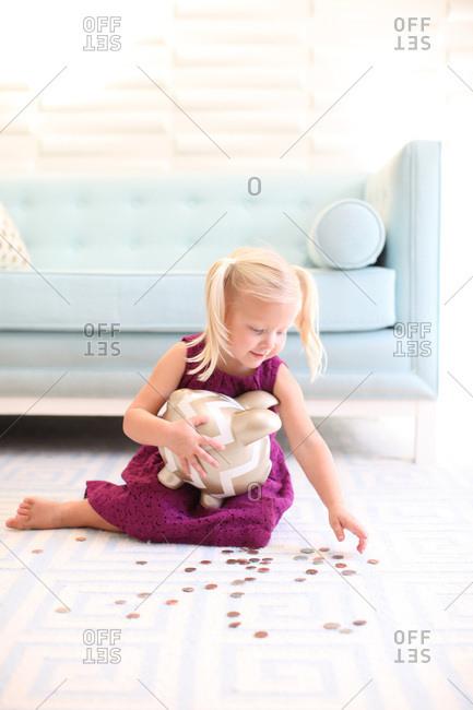Preschool girl sitting on floor putting money in her piggy bank