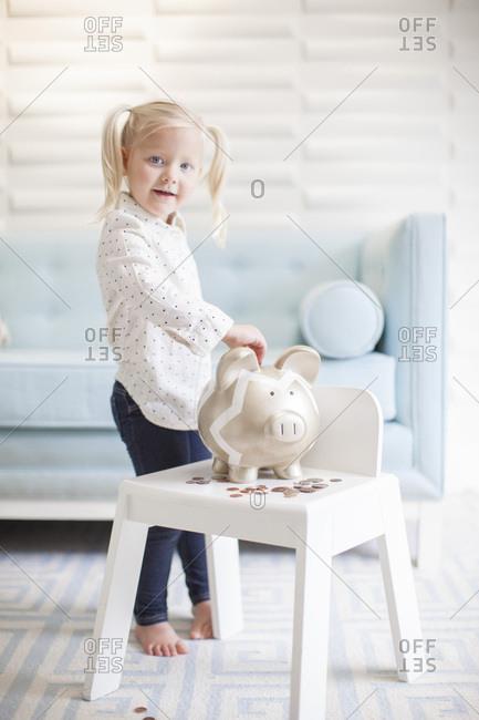 Preschool girl putting money in her piggy bank