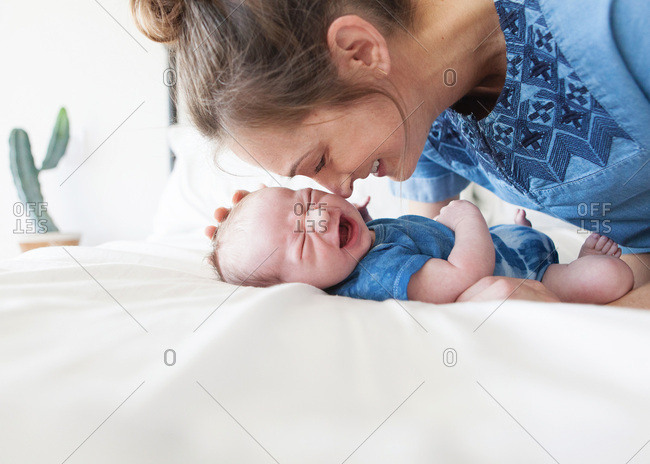 Mother kissing her newborn baby while he is crying