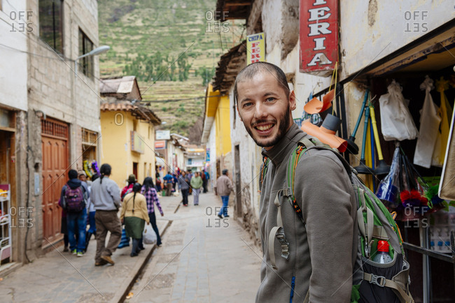 Valle Sagrado, Peru - May 10, 2015: Tourist with backpack walking on a commercial street in the city center in Pisac, Valle Sagrado, Peru