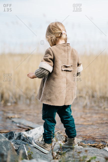 Rear view of little girl throwing stones into a lake