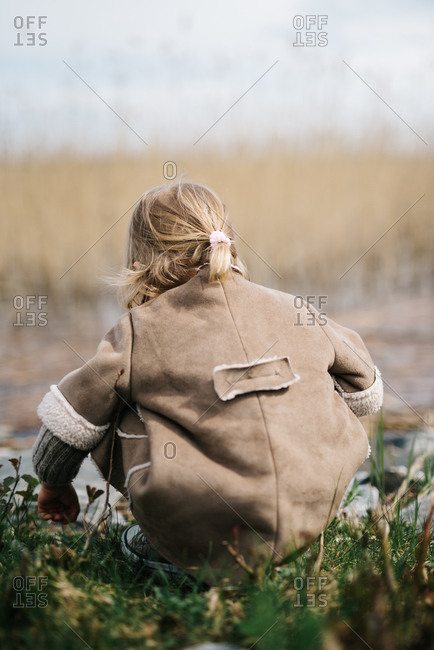 Rear view of little girl overlooking lake
