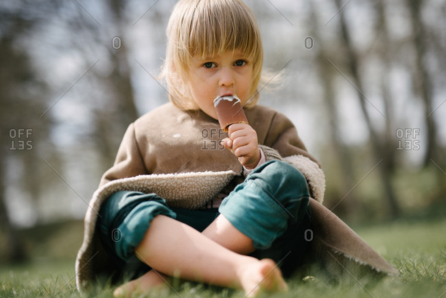 Little girl eating chocolate covered ice cream treat