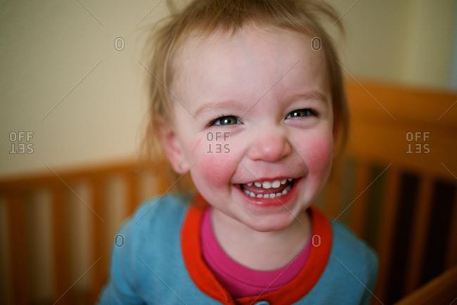 Little girl smiling in crib