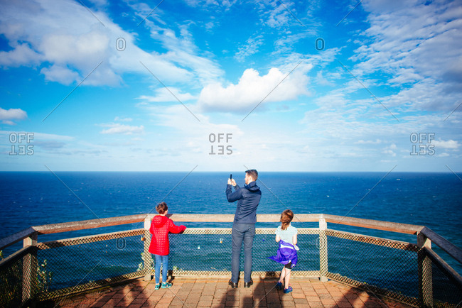 Father and daughters overlooking blue ocean and cloudy sky