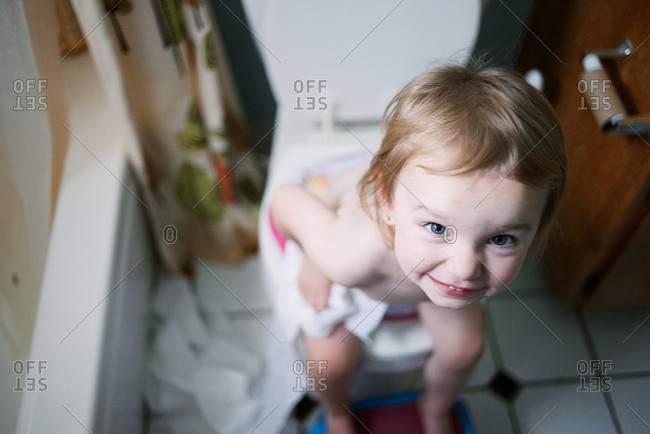 Girl using all the toilet paper while sitting on the toilet