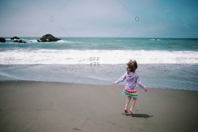 Girl jumping in front of ocean