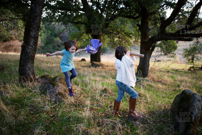 Girls playing in rural field with trees