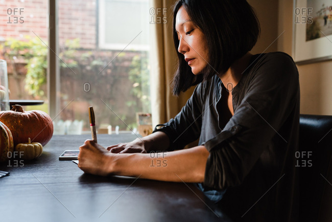 Asian woman sitting at the table writing a letter