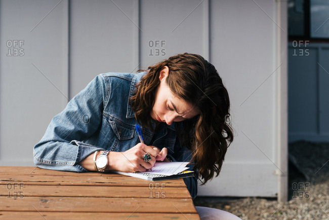 Woman sitting at an outdoor table writing a letter