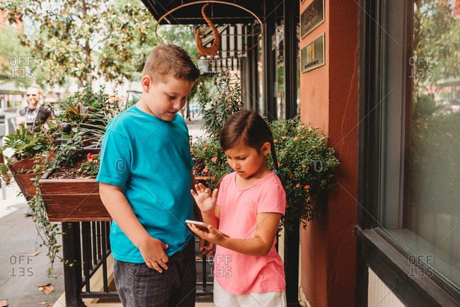 Two kids checking a cell phone