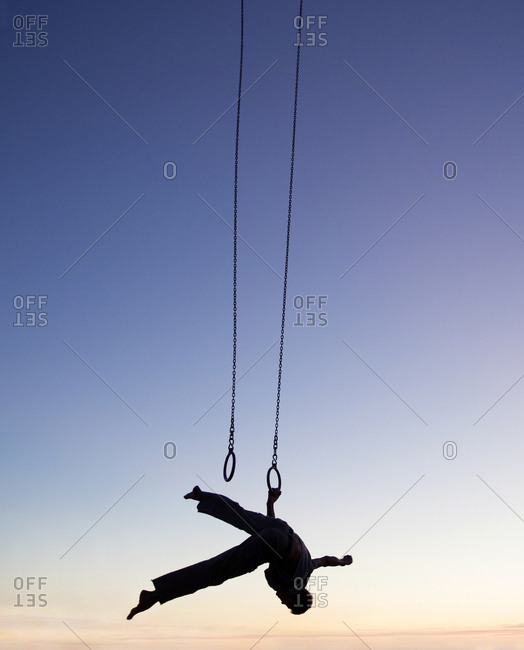 Man on rings in silhouette