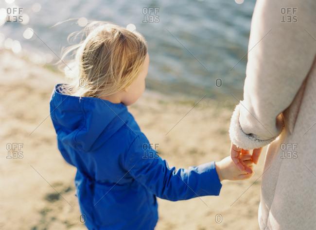 Toddler girl at seashore with woman