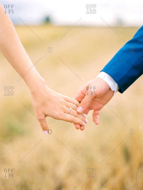 Bridal couple joining hands outdoors