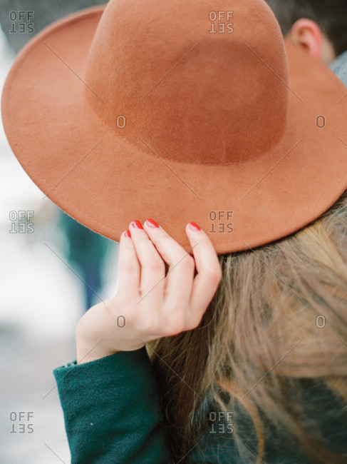 Woman covering face with hat