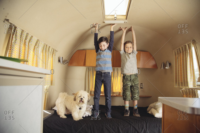 Brothers standing with arms raised on bed in motorhome