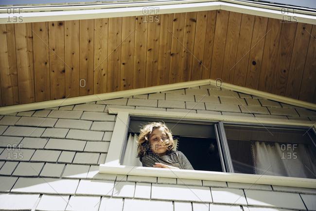 Low angle view of smiling boy peeking through house window