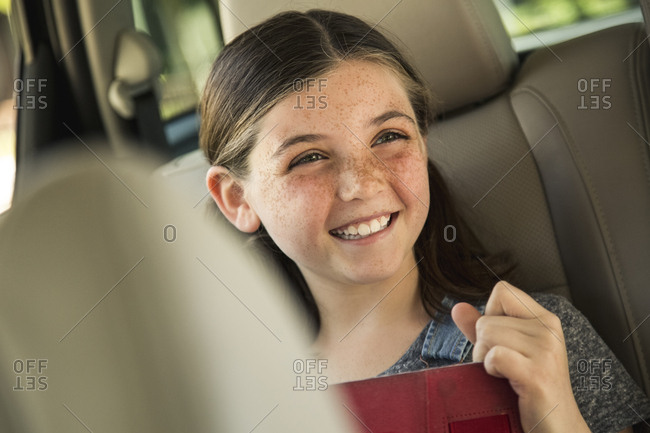 Happy girl holding digital table in back seat of car