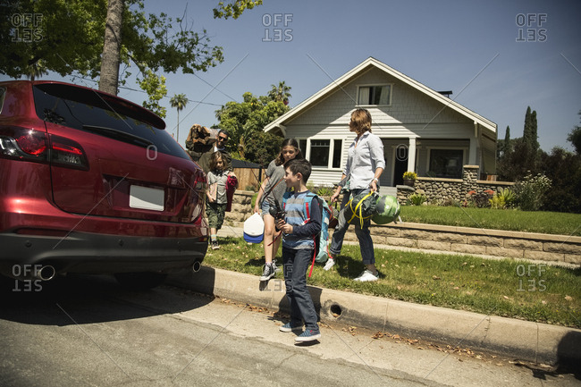 Family carrying camping gear while standing by SUV outside house
