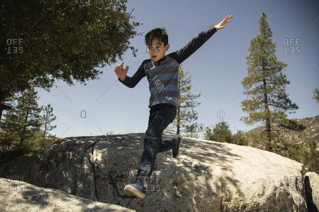 Low angle view of boy jumping on rocks in forest against clear blue sky