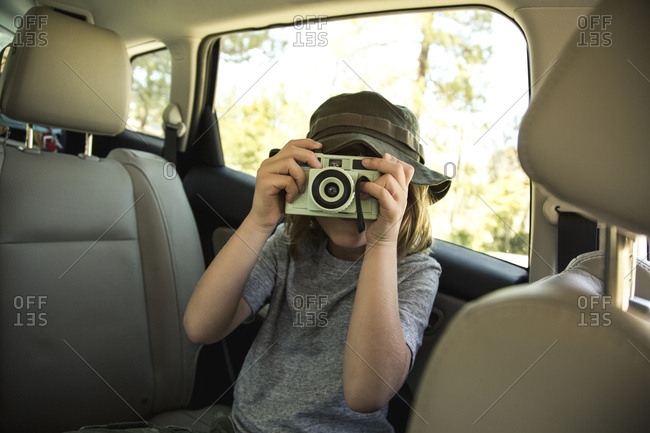 Boy photographing through retro camera in car while going for camping