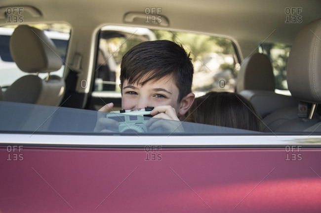 Portrait of cute boy holding old fashioned camera in car while going camping