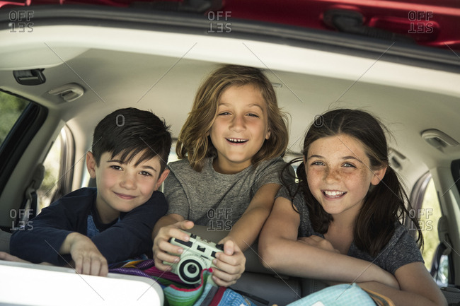 Portrait of happy siblings with camera in back seat of car
