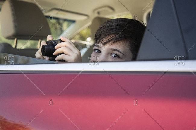 Portrait of cute boy holding digital camera in car