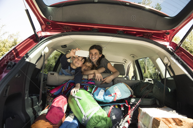 Happy siblings taking selfie through smartphone in car packed for vacation