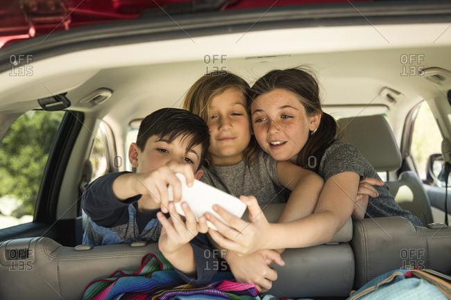 Siblings taking selfie through smartphone in car
