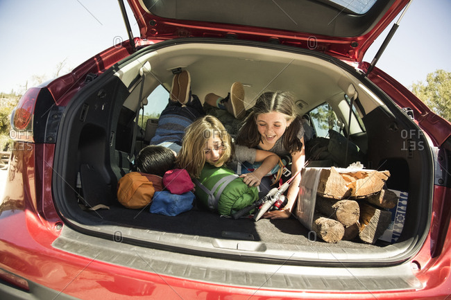 Happy kids in back of car packed with camping gear in car trunk during summer vacation