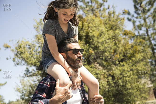 Father carrying daughter on shoulders during sunny day while camping in forest