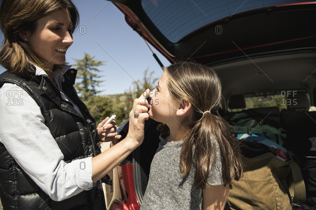 Mother applying sunscreen on daughter's nose while standing outside car during vacation